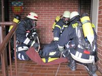 Der Atemschutzgeräteträger wird behutsam ins Rettungstuch gelegt.
