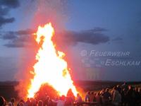 Am wärmenden Feuer sitzen die Menschen gemütlich beisammen.