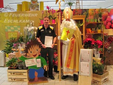 Der Kamperl, die Leitfigur zur Brandschutzerziehung der Feuerwehr Eschlkam, bietet die Bastelbögen zum Umrüsten auf einen Nikolaus im Geschäft an.